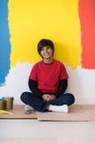 休息在绘的年轻男孩画家墙壁以后 库存图片