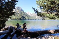 休息在Estany de Sant Maurici湖的年轻美丽的妇女,在长的早晨高涨以后在Aiguestortes国家公园, Pyrenee 免版税库存图片