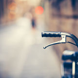 休息在Narow街道的一辆老自行车的把手 免版税库存照片