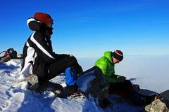 休息在Peleaga峰顶,罗马尼亚顶部的两个年轻登山人 免版税库存图片