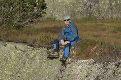 休息坐一个岩石的远足者在阿尔卑斯 库存图片
