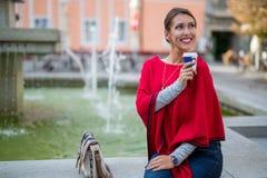 休息外面在井的美丽的年轻女人,当喝咖啡时 免版税库存图片