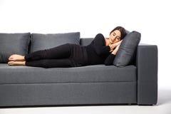 休息她的在一个枕头的妇女头在白色的一个长沙发 库存图片