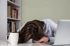 休息她的在桌上的疲乏的女孩头与计算机一起使用 图库摄影