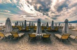 休息室太阳床和伞在热带海滩日出早晨 免版税库存图片