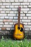 休息对一个白色砖墙的声学吉他 免版税图库摄影