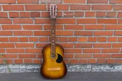休息对红砖墙壁的声学吉他 库存照片
