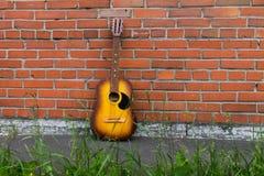 休息对红砖墙壁的声学吉他 免版税图库摄影