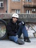 休息对都市年轻人的骑自行车的人听的音乐 免版税库存图片