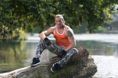 休息户外在自然Afther锻炼的可爱的人 免版税库存照片