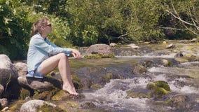 休息旅游的妇女坐石河岸和,当夏天高涨时 股票视频