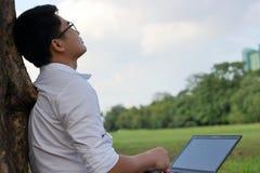 休息时间 看天空的亚裔年轻人在工作以后反对他的膝上型计算机 免版税图库摄影
