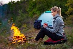 休息由在一个帐篷的背景的火的妇女旅客在他的小径的通过山和森林 免版税图库摄影