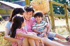 休息由有古板的周期的篱芭的亚洲家庭 免版税库存照片
