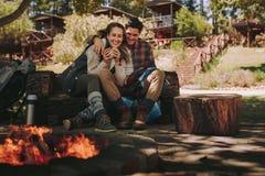 休息由篝火的爱恋的夫妇在露营地 免版税库存照片