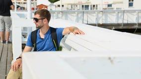 休息男性的背包徒步旅行者坐码头和,看海和海滩,序列 影视素材