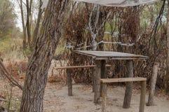 休息的地方与木桌和椅子 对野餐在河的森林里 库存图片