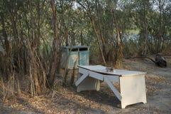 休息的地方与木桌和椅子 对野餐在河的森林里 免版税库存照片