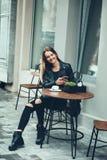 休息的时刻!坐在咖啡馆的流行的服装的美丽的少妇拿着巧妙的电话和享受天气 免版税库存照片