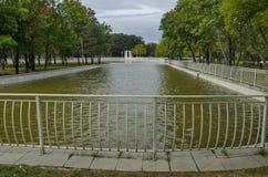 休息的普遍的北部公园与秋季老森林、长木凳和湖在Vrabnitsa区 免版税库存照片