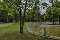 休息的普遍的北部公园与秋季老森林、长木凳和湖在Vrabnitsa区 库存图片