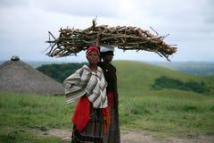 休息非洲的妇女,当运载木头在南非时 免版税库存照片