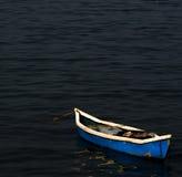 `休息` -一条蓝色小船所有单独在镇定和平静的海水 免版税库存照片