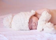 休眠与被编织的帽子和手套的小婴孩 免版税图库摄影
