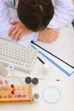 休眠在与医疗东西的服务台上的医生 免版税库存照片