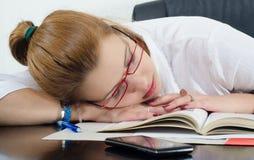 休眠在书的疲乏的学员而不是学习 免版税库存照片