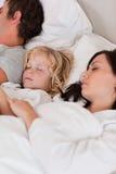 休眠在他的父项之间的男孩的纵向 免版税库存照片