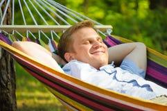 休眠在吊床的年轻人 免版税库存照片