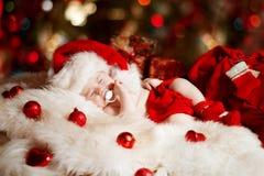 休眠在圣诞老人帽子的圣诞节新出生的婴孩 免版税库存照片