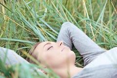 休眠在草的平静的妇女 库存图片