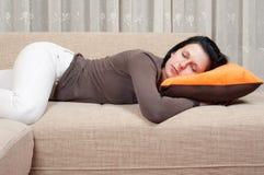 休眠在长沙发的俏丽的妇女 库存照片