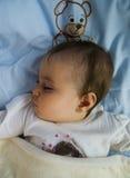休眠的女孩在与玩具熊的河床上 免版税库存照片