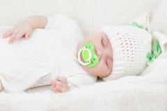 休眠的婴儿女婴在兔宝宝盖帽穿戴了 库存图片