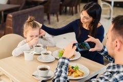 休闲、技术、生活方式和人概念-与拍食物的照片智能手机的愉快的家庭在餐馆 库存图片