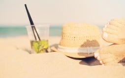 休闲在夏天-美好性感的妇女脚、女性腿在沙滩与帽子和mojito鸡尾酒 在的Mojito鸡尾酒 免版税库存照片