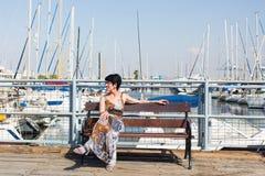 休闲妇女在度假在游艇和风船小游艇船坞度假村附近的 豪华生活方式 免版税库存照片