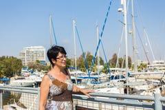 休闲妇女在度假在游艇和风船小游艇船坞度假村附近的 豪华生活方式 免版税库存图片