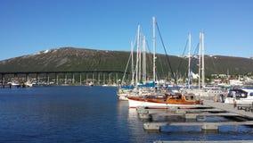 休闲小船在tromsoe城市在明亮的夏天阳光下怀有 免版税图库摄影
