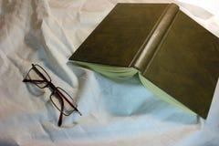 休闲项目,玻璃,书,安置在一件机织织物 库存图片