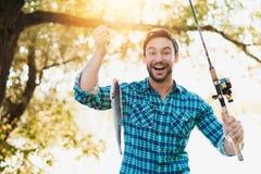 优秀抓住 一件蓝色衬衣的一个人快乐显示一条鱼对照相机,他风行转动 库存照片