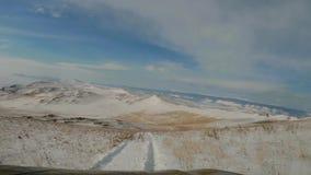 优秀越野冒险 乘坐在Olkhon积雪的小山的SUV  贝加尔湖和Pribaikalskiy土坎 股票录像