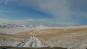 优秀越野冒险 乘坐在Olkhon积雪的小山的SUV  贝加尔湖和Pribaikalskiy土坎 影视素材
