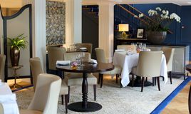 优等的典雅和现代餐馆在阿姆斯特丹,荷兰在欧洲 位子、桌和灯在豪华优质旅馆 免版税库存照片