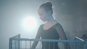 优美的专业芭蕾舞女演员跳舞画象在黑礼服的在蓝色笼子里面的演播室在a的聚光灯 股票录像