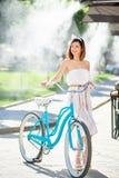 优美的女孩在夏天拿着蓝色葡萄酒自行车 免版税库存照片
