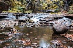 优美的瀑布在一座石桥梁附近流动 图库摄影